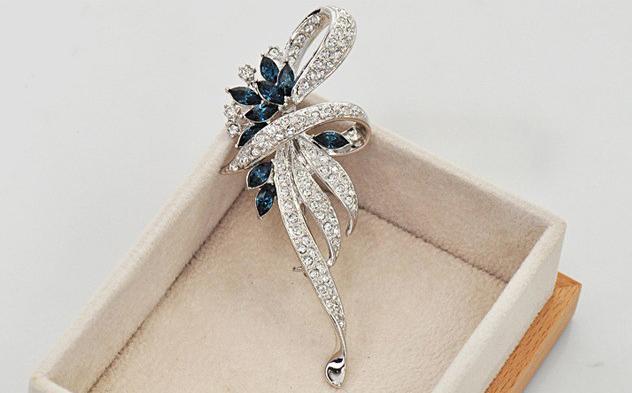 Luxusná brošňa v tvare ornamentu v striebornej farbe s tmavo modrými kryštálmi