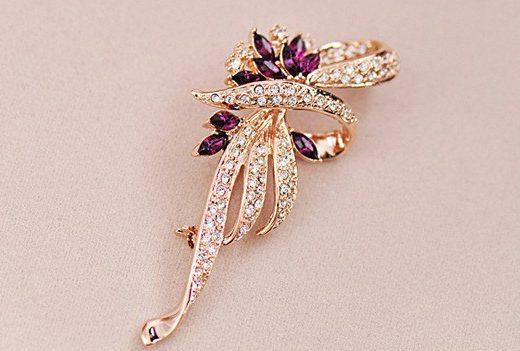 Luxusná brošňa v tvare ornamentu v zlatej farbe s fialovými kryštálmi
