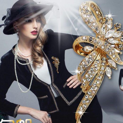 Luxusná brošňa v tvare ornamentu v zlatej farbe s bielymi kryštálmi